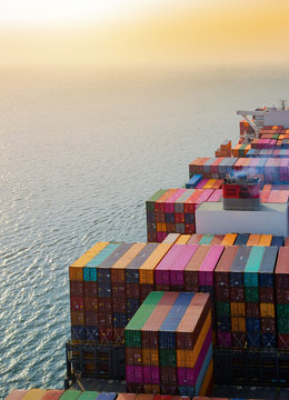 top aerial view of the large volume of TEU containers on ship sailing in the sea carriage the shipment from loading port to destination,  heading to the destination of success light