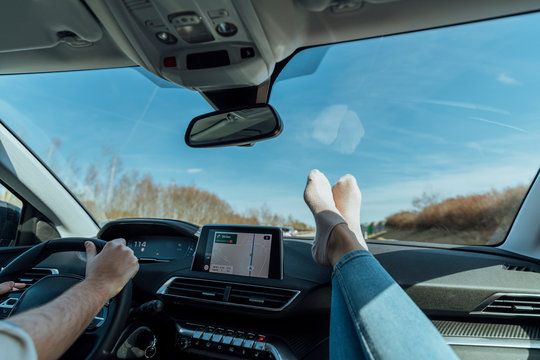 Heterosexual couple in a luxury car, making a road trip, the man has his hands on the steering wheel and the woman has her feet with some socks on the dashboard.