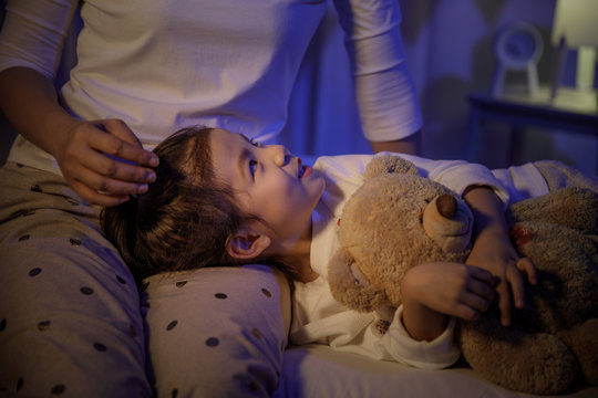 Mother stroking head of cute girl then sleeping on mom lap on bed in a dark bedroom at night, Child asian girl hug teddy bear, Comfortable children at home concept