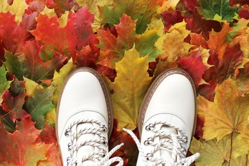The Golden autumn season and the concept of weather. Beige boots on a carpet of autumn leaves....