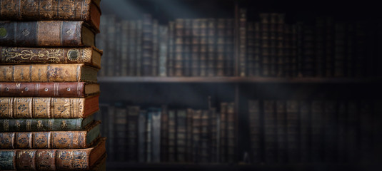 Old books on wooden shelf and ray of light. Bookshelf history theme grunge background. Concept on...
