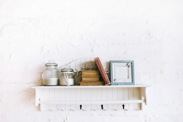 Handmade wooden shelf with books, picture frame and candles in glass bottles. Cozy rustic style, white background. Stucco molding wall.