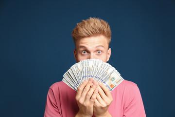Portrait of surprised lottery winner with money fan on blue background