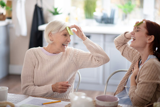 Laughing pensioner playing words game with nurse