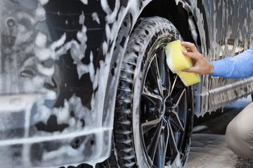 Businessman cleaning auto with sponge at self-service car wash, closeup