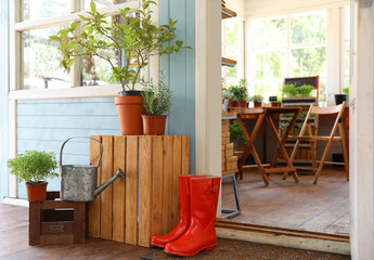 Rubber boots, watering can and plants on wooden crates near house outdoors. Gardening tools