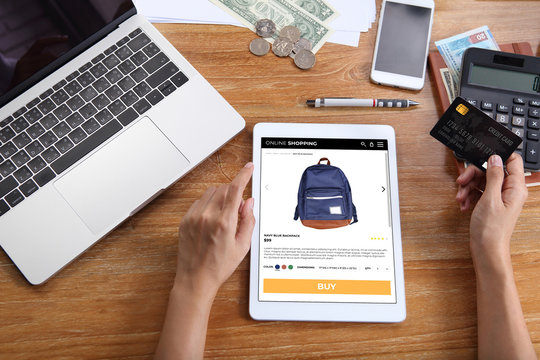 woman using credit card for buy navy blue backpack on ecommerce website via tablet with laptop, smartphone and office stationery on wooden desk