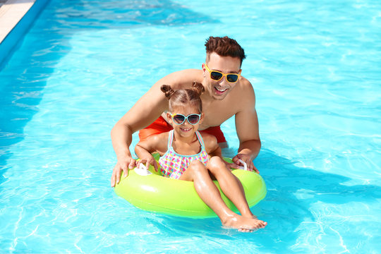 Happy father and little daughter with inflatable ring in swimming pool