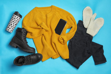 Fototapete - Flat lay composition with winter clothes and boots on light blue background