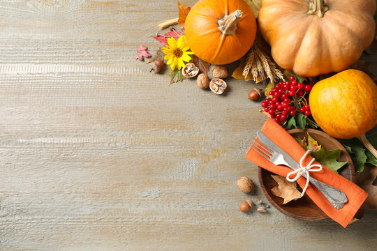 Autumn vegetables and cutlery on wooden background, flat lay with space for text. Happy Thanksgiving day