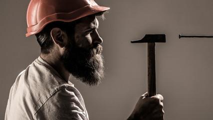 Fototapeta Builders in hard hat, helmet. Bearded man worker with beard, building helmet, hard hat. Handyman, hammer, man builder, industry, technology, builder concept. Hammer hammering a nai obraz