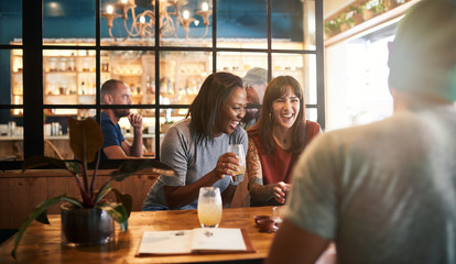 Diverse young friends laughing over drinks together in a bar