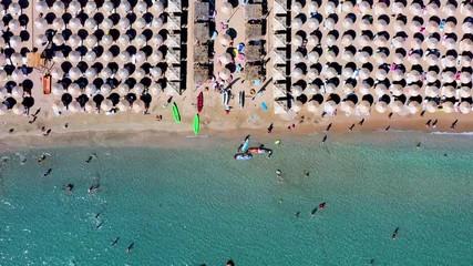 Wall Mural - Top down Luftaufnahme eines Strandes mit Sonnenschirmen in der Reihe und Leute die im türkisem Wasser Spaß haben, bei Athen, Griechenland