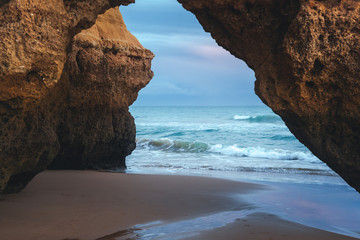 Wall Mural - Beautiful red arch framing the ocean and the horizon on Algarve Beach at sunset