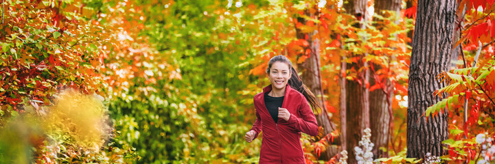 Fit woman on autumn trail run running in foliage forest banner background. Healthy active lifestyle Asian young runner training cardio on fall park jogging outdoors.