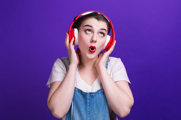 Funny girl singing in big red headphones isolated at blue background on studio.