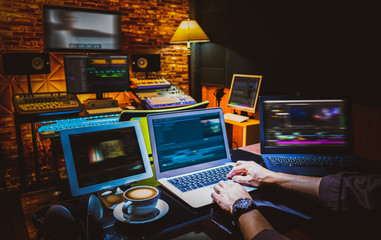 professional director, editor, producer editing movie footage and music score track on computer in digital editing, post production, broadcasting studio Wall mural