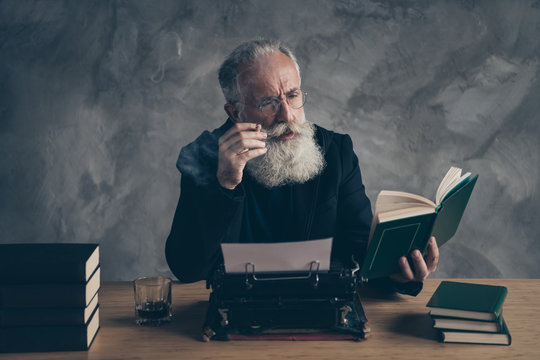 Portrait of his he nice attractive content dreamy bearded gray-haired professional expert publisher reading interesting diary life story novel over concrete wall background