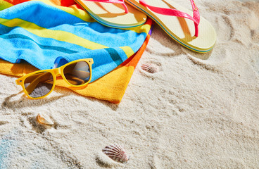Colorful beach towel, sunglasses and thongs