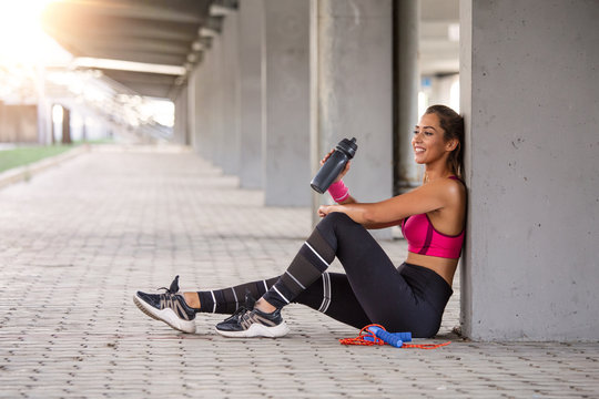 Fitness woman Relaxing after exercise with a whey protein bottle. Relaxing after training. Beautiful young woman looking away while resting after running