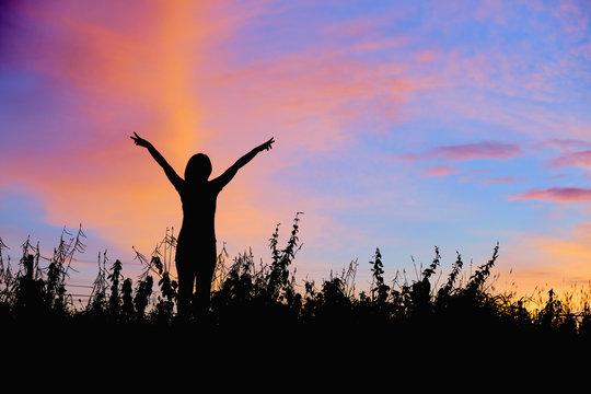 Silhouette of women with hands up Against the sunrise background