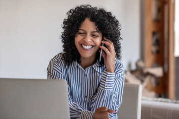 Laughing female entrepreneur talking with a client on her cellphone