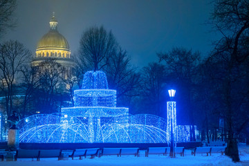 Festive St. Petersburg. Russia. View of the city at Christmas. Fountain of lights on St. Isaac square. The fountain is decorated with garlands. Lights evening city. Isaakievsky cathedral.