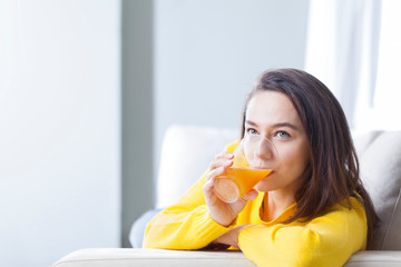 Foto op Plexiglas Sap Young woman drinking orange juice