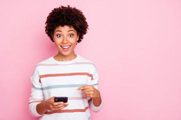 Photo of pretty dark skin curly lady holding telephone watching likes reading comments wear white...