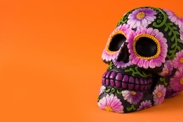 Typical Mexican skull with flowers painted on orange background. Dia de los muertos. Copy space