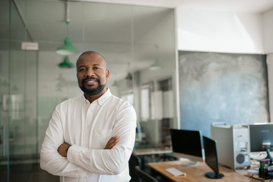 Smiling African American businessman standing alone in a large office