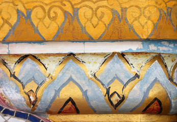 Elements from a weathered old Buddhist temple wall form a colorful ethnic background of gold, orange and sky blue designs.