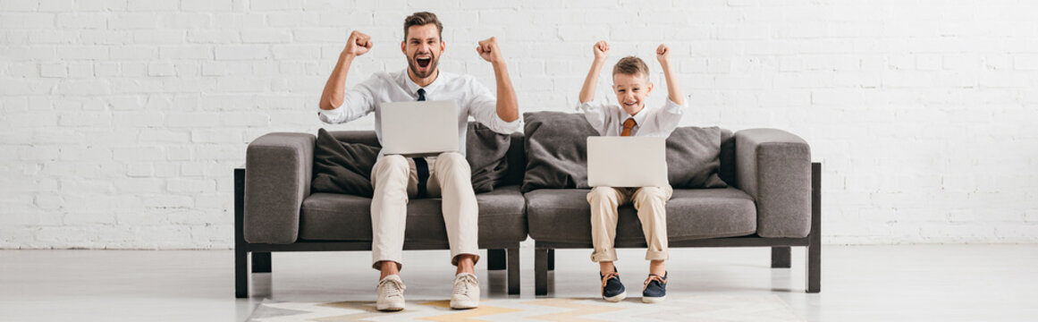 panoramic shot of smiling dad and son sitting on sofa with laptops and showing yes gestures