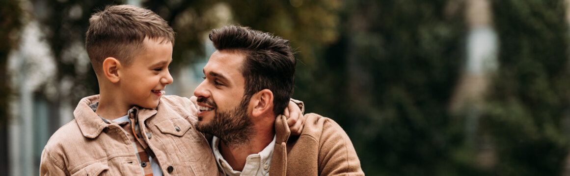 panoramic shot of smiling son and dad embracing and looking at each other in autumn day on street