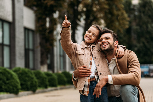 happy father and son embracing on street in autumn day