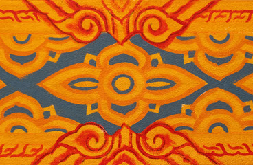 Elements from a symmetrical red and orange pattern painted on the wall of an ancient Buddhist temple in south east Asia