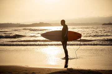 Surfer with surfboard on the beach at sunset or sunrise. Adventure surf advertising image