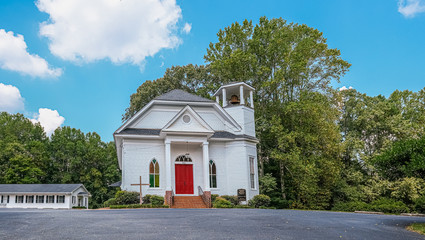 Small White Church with Red Door by Trees on a Hill