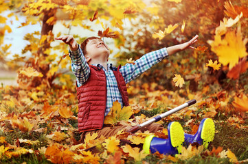 Boy sitting on the ground throwing autumn leafs in the air
