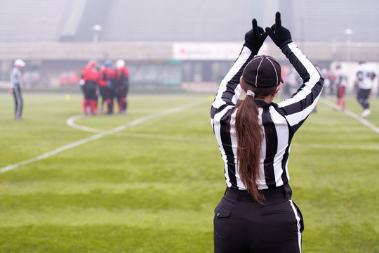 rear view of female american football referee
