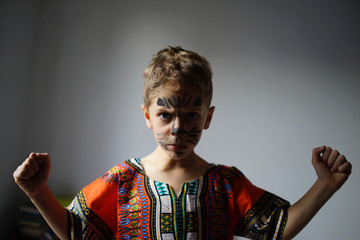 Young boy with painted face - serious, strong expression