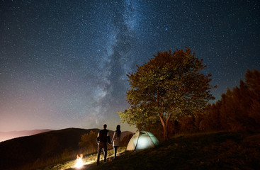 Rear view of happy couple tourists standing at bonfire near glowing tent, holding hands under amazing night sky full of stars and Milky way. On the background starry sky, mountains and big tree
