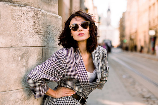 Trendy fashion woman in jacket and sunglasses walking on the street, urban city scene. Copy space