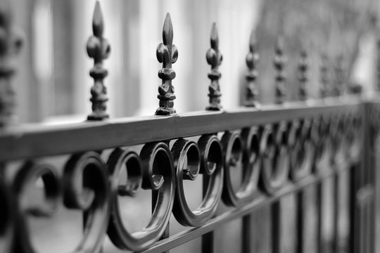 Black wrought iron front garden. Metal fence made of forged steel. Close up