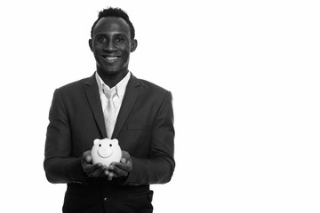 Young happy black African businessman smiling and holding piggy bank