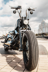 The front wheel of the motorcycle with a drum brake and a cable to it is the front fork with a shock absorber and a spring on a homemade motorcycle in a vintage style