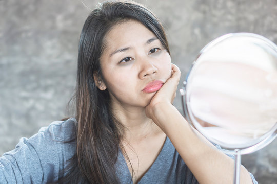 unhappy Asian woman age 40 checking her dark eyes circle problem in mirror