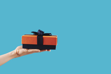 Small gift wrapped in blue and orange paper in hand of person, isolated on blue