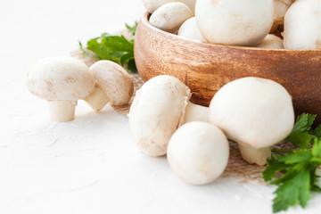 Fresh mushrooms champignon in brown bowl on white background.