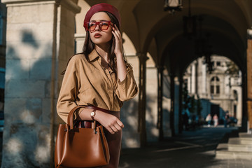Outdoor, street style, fashion portrait of elegant, luxury woman wearing faux leather dark red beret, sunglasses, beige shirt, wrist watch, holding brown handbag, posing in European city. Copy space Wall mural